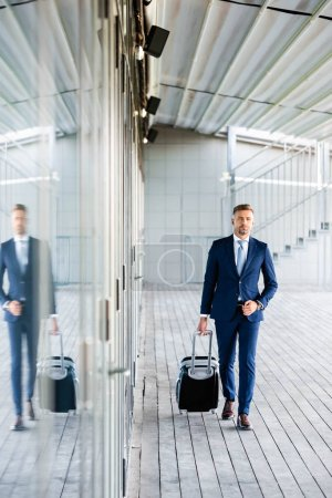 Photo for Handsome and confident businessman in formal wear holding suitcase - Royalty Free Image