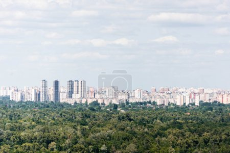 Photo pour Urban scene with trees in city park, skyscrapers and buildings - image libre de droit