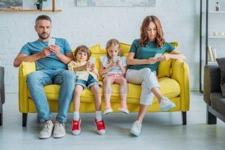 Photo pour Famille attentive assis sur un canapé jaune à la maison et en utilisant des smartphones - image libre de droit