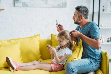 Photo pour Père toucher les cheveux des filles tout en étant assis sur le canapé et en utilisant des smartphones ensemble - image libre de droit