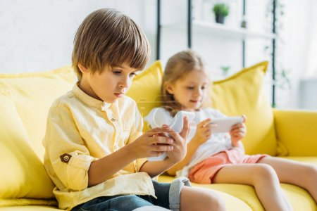 Photo for Selective focus of cute boy with sister sitting on sofa and using smartphones at home - Royalty Free Image