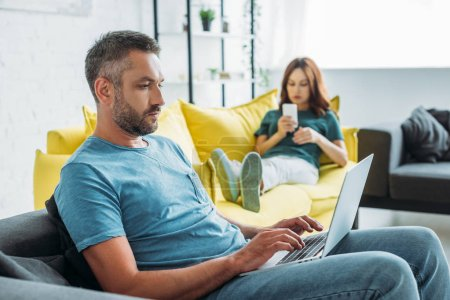 foyer sélectif de l'homme sérieux en utilisant un ordinateur portable tout en étant assis sur le canapé près de la femme en utilisant smartphone