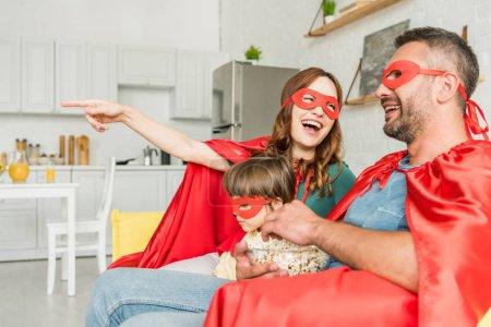 Photo pour Mère gaie pointant avec le doigt pourquoi la famille dans les costumes des super-héros s'asseyant sur le sofa et regardant la tv - image libre de droit