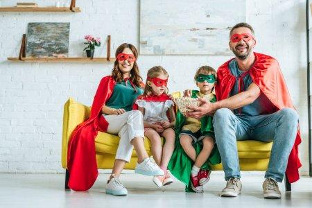 Photo pour Famille heureuse dans des costumes des super-héros mangeant le maïs éclaté et regardant la tv à la maison - image libre de droit