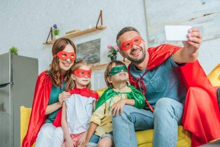 Photo pour Famille heureuse dans des costumes des super-héros prenant le selfie sur le smartphone tout en s'asseyant sur le divan à la maison - image libre de droit