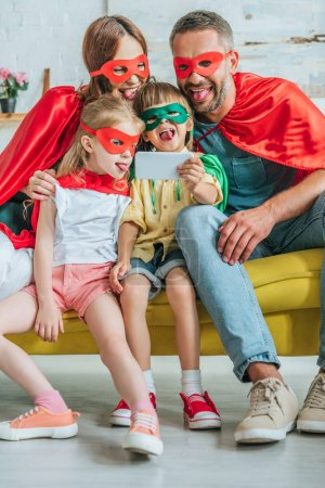 Photo pour Famille gaie dans des costumes de super-héros collant des langues dehors tout en prenant le selfie sur le smartphone à la maison - image libre de droit