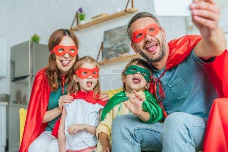 Photo pour Foyer sélectif de la famille heureuse dans les costumes de super-héros collant des langues dehors tout en prenant le selfie sur le smartphone à la maison - image libre de droit