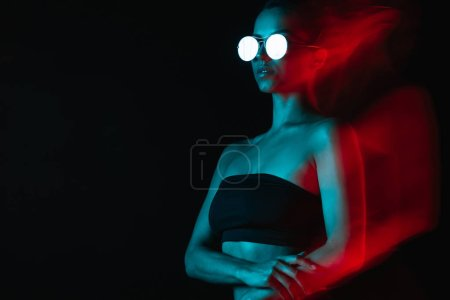 Photo for Motion blur of pretty woman in sunglasses on black - Royalty Free Image