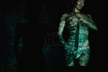 Photo for Cropped view of undressed young woman with shadows and light on body standing on black - Royalty Free Image