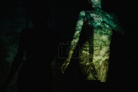 Foto de Vista recortada de una joven desnuda con sombras en el cuerpo de pie sobre negro - Imagen libre de derechos
