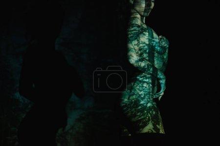Foto de Vista recortada de mujer desnuda con sombras en el cuerpo de pie sobre negro - Imagen libre de derechos