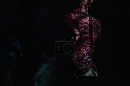 Foto de Vista recortada de una chica desnuda con sombras en el cuerpo de pie sobre negro - Imagen libre de derechos