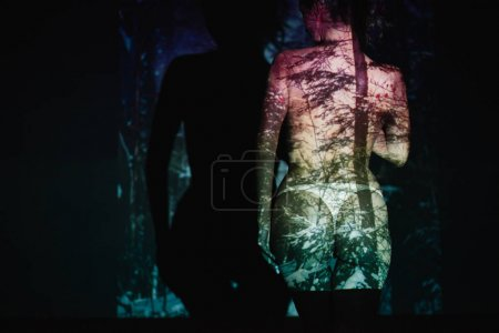 Photo for Back view of young woman with shadows on body standing on black - Royalty Free Image