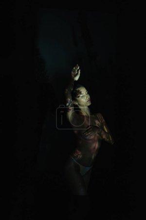 Photo pour Fille déshabillée avec les yeux fermés et les ombres sur le corps debout sur noir - image libre de droit