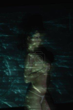 Photo pour Flou de mouvement de fille debout et couvrant les seins sur noir - image libre de droit