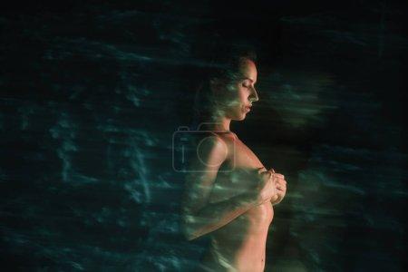 Foto de Desenfoque de movimiento de chica desnuda de pie y cubriendo los pechos cerca de los pinos en negro - Imagen libre de derechos