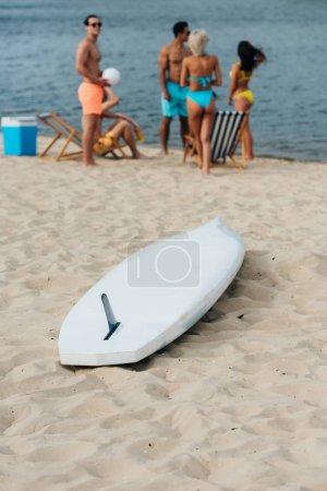 Photo pour White surfing board on sand near multicultural friends resting on beach - image libre de droit