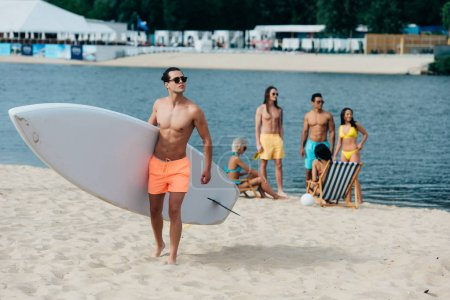 Photo for Handsome man holding surfboard while multicultural friends resting on riverside - Royalty Free Image