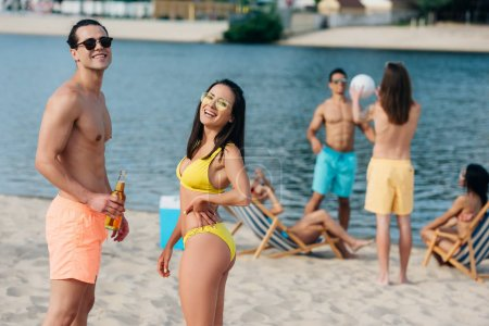 Photo for Cheerful young man and woman with bottles of beer smiling at camera while standing on beach near multicultural friends - Royalty Free Image