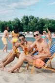 """Постер, картина, фотообои """"красивый мультикультурных друзей проведения бутылки пива и улыбается на камеру, сидя в шезлонги на пляже"""""""