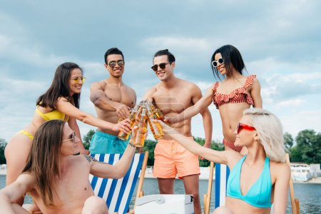 Photo for Cheerful multicultural friends clinking bottles of beer while having fun on beach - Royalty Free Image
