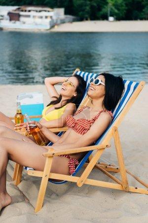Schöne multikulturelle Mädchen sitzen am Strand in Chaiselongs mit Bierflaschen