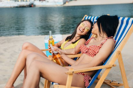 Photo for Beautiful multicultural girls holding bottles of beer while sitting on beach in chaise lounges - Royalty Free Image