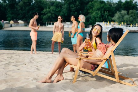 Photo for Cheerful multicultural girls drinking beer in chaise lounges near friends resting on beach - Royalty Free Image
