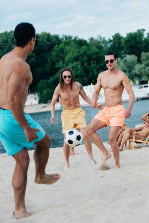 Photo pour Beaux, jeunes hommes multiculturels jouant au football sur la plage - image libre de droit