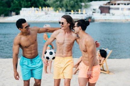 Foto de Cheerful, young multicultural friends hugging friend holding soccer ball on beach - Imagen libre de derechos