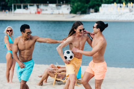 Photo for Cheerful, young multicultural friends having fun with soccer ball on beach - Royalty Free Image