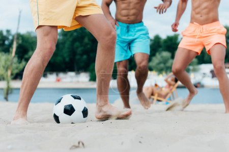 Photo for Cropped view of young multicultural men playing football on beach - Royalty Free Image