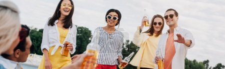 Photo pour Photo panoramique d'amis multiculturels gais avec des bouteilles de bière s'amusant sur la plage - image libre de droit