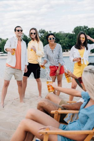 Photo for Young multiethnic friends holding bottles of beer while having fun on beach - Royalty Free Image
