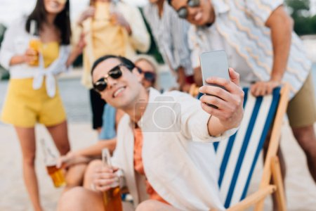 Photo for Selective focus of cheerful young man taking selfie with multicultural friends having fun on beach - Royalty Free Image