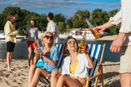 young, cheerful multicultural men and women drinking beer while resting on beach
