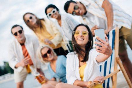 Foto de Enfoque selectivo de atractiva joven tomando selfie con amigos multiculturales divirtiéndose en la playa - Imagen libre de derechos