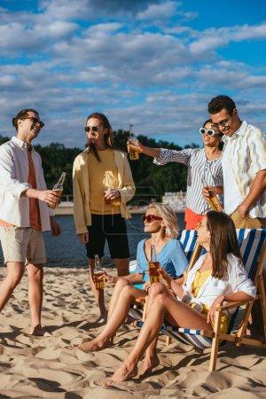 fröhliche multikulturelle Freunde beim Biertrinken am Strand