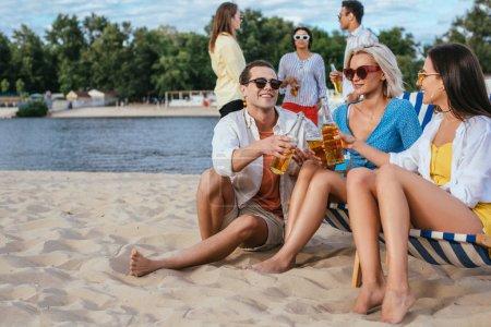Foto de Jóvenes amigos multiculturales hablando y bebiendo cerveza mientras se divierten en la playa - Imagen libre de derechos