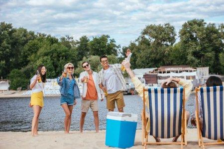 fröhliche multikulturelle Freunde mit Bierflaschen am Strand