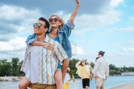 Photo for Handsome bi-racial man piggybacking girlfriend while walking on beach near multicultural friends - Royalty Free Image