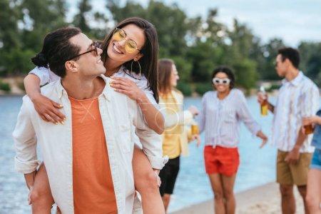 Foto de Apuesto joven piggybacking novia mientras se divierte en la playa junto con amigos multiculturales - Imagen libre de derechos