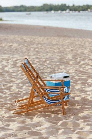 Photo pour Deux chaises longues et réfrigérateur portatif sur la plage de sable près de la rivière - image libre de droit
