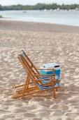 """Постер, картина, фотообои """"два шезлонга и портативно холодильник на песчаном пляже возле реки"""""""