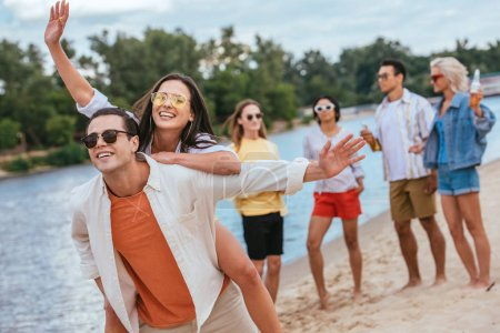 Photo for Cheerful young man piggybacking happy girlfriend while walking on beach together with multicultural friends - Royalty Free Image