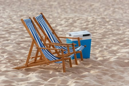 Photo for Two chaise lounges and cooler box on sunny beach - Royalty Free Image