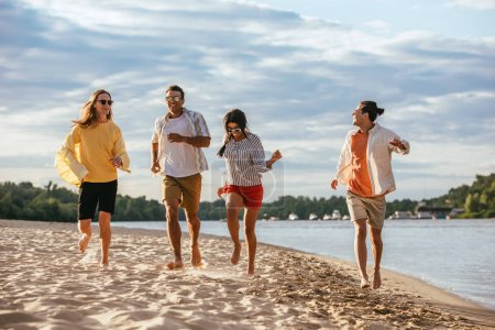 cheerful multicultural friends running on sand beach near river