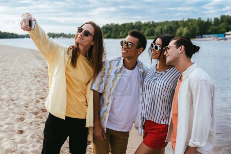 Photo for Smiling young man taking selfie with cheerful multicultural friends on beach - Royalty Free Image