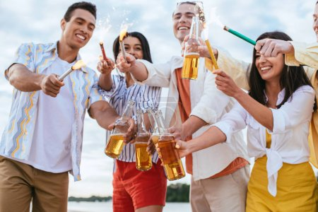Photo for Happy multicultural friends holding sparklers and bottles of beer while having fun on beach - Royalty Free Image