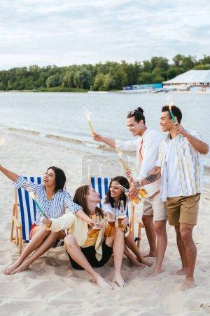 Foto de Alegres amigos multiculturales sosteniendo botellas de cerveza y chispas mientras se divierten en la playa - Imagen libre de derechos